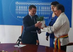 "The ""Forget-me-not"" flower is handed over by Mircea-Valer Pauca, a person with High-functioning autism"