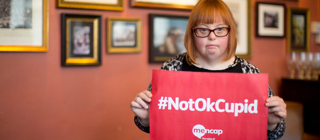 Kate Brackley from mencap holding a sign with #NotOkCupid written on it